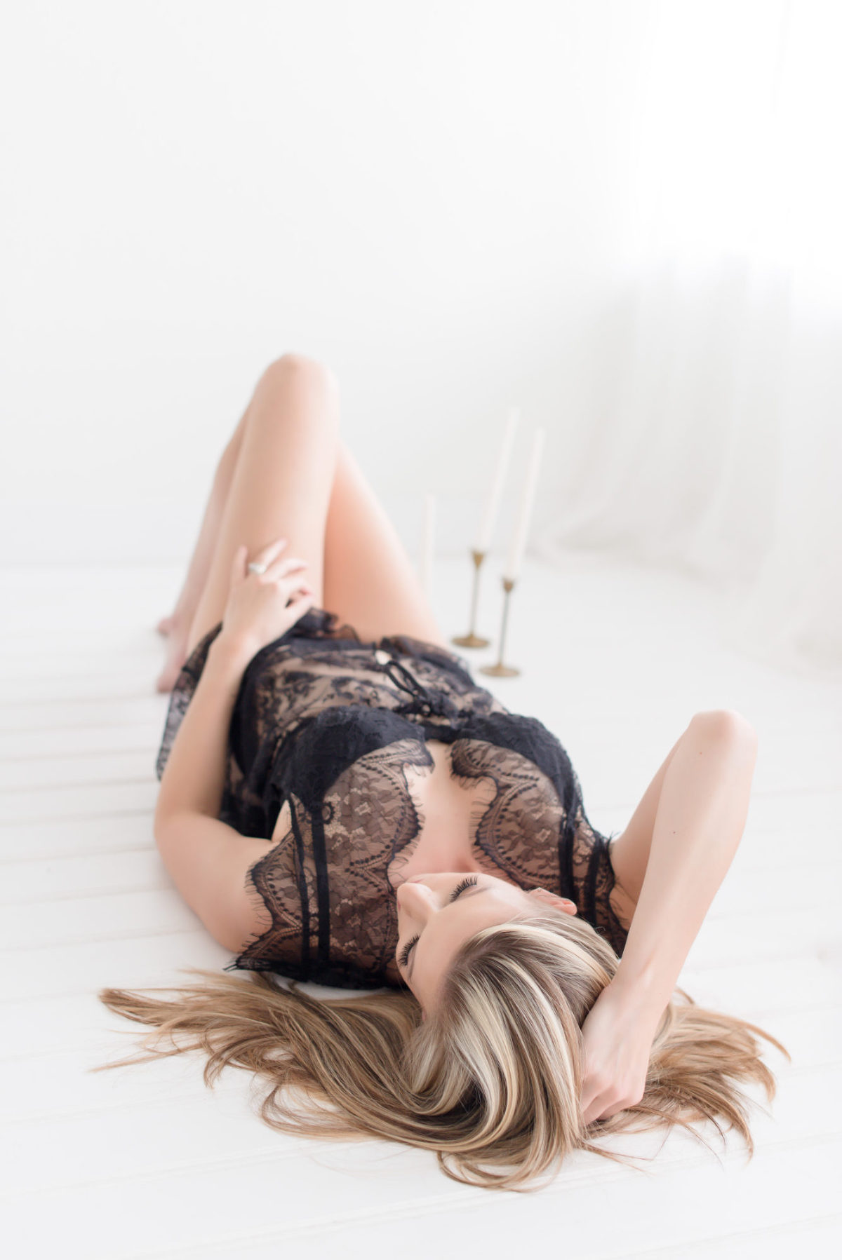beautiful woman laying on the floor with candles surrounding her for her boudoir session